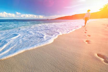 barefoot women: Woman at beautiful beach at Seychelles walking on sand. Focus on footprints.