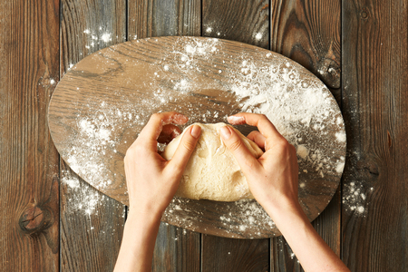 female hands: Female hands kneading dough on wooden table