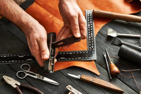 herramientas de trabajo: Hombre que trabaja con el cuero que hacen a mano usando herramientas de bricolaje