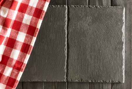 dark grey slate: Empty slate plates and tablecloth over black wooden background Stock Photo