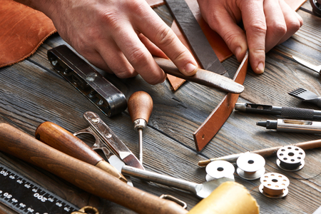 Man working with leather using crafting DIY tools Banque d'images