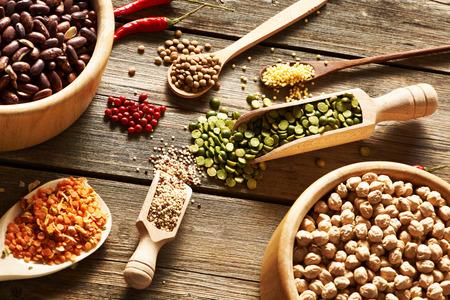 legumbres secas: Tazones y cucharas de diversas legumbres en fondo de madera