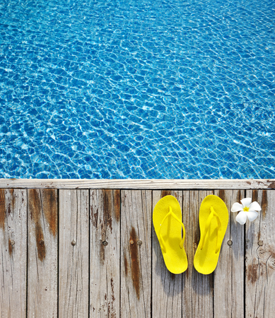wooden shoes: Yellow flip-flops by a swimming pool Stock Photo