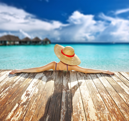 Woman in hat relaxing at beach jetty Stock Photo