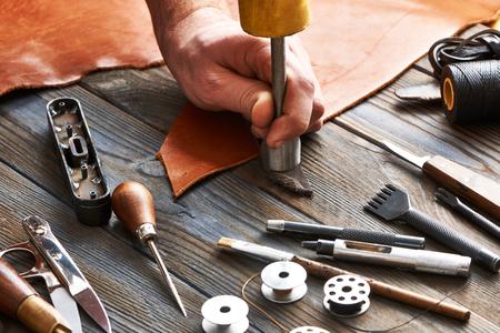 Hombre que trabaja con el cuero que hacen a mano usando herramientas de bricolaje Foto de archivo - 55276856