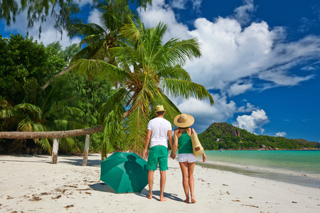 praslin: Couple in green on a tropical beach at Seychelles