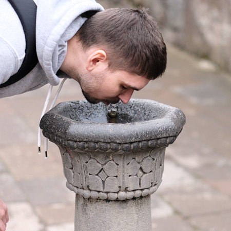 man drinking water: Man drinking water from fountain at street
