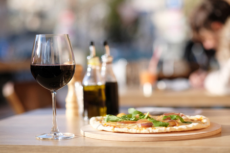 food and wine: Pizza and glass of red wine in outdoor restaurant
