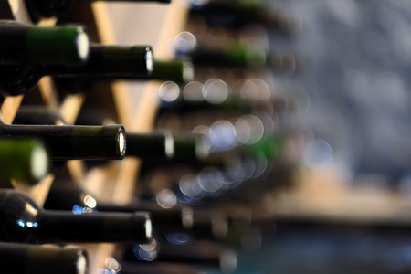 Resting wine bottles stacked on wooden racks in cellar 스톡 콘텐츠