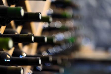 Resting wine bottles stacked on wooden racks in cellar Standard-Bild