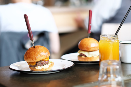 cheeseburgers: Cheeseburgers and lemonade in jar on table