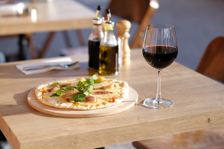 glass of red wine: Pizza and glass of red wine in outdoor restaurant