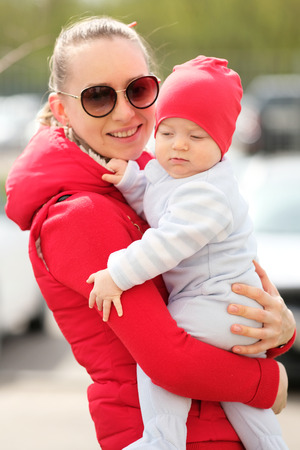 six months: Six months old baby boy with his mother outdoors