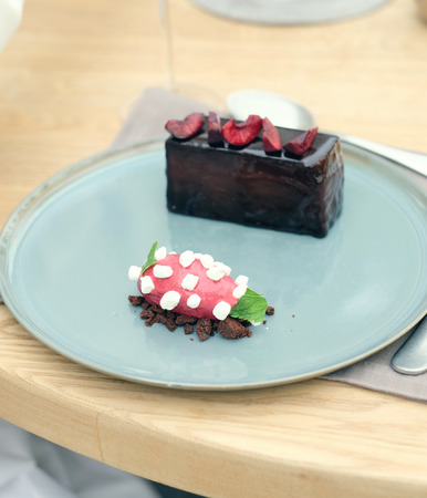 chocolate treats: Chocolate cake with sorbet in outdoor restaurant Stock Photo