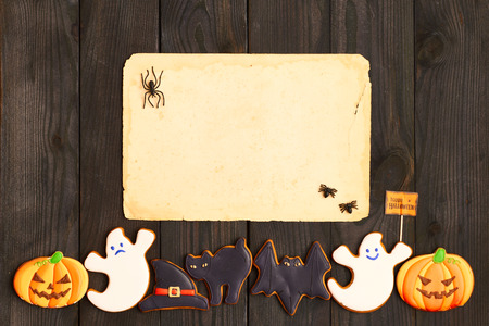 papier a lettre: Blank old paper sheet and gingerbread cookie over dark wooden background. Halloween invitation. Banque d'images