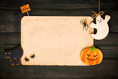 Blank old paper sheet and gingerbread cookie over dark wooden background. Halloween invitation. Stock Photo