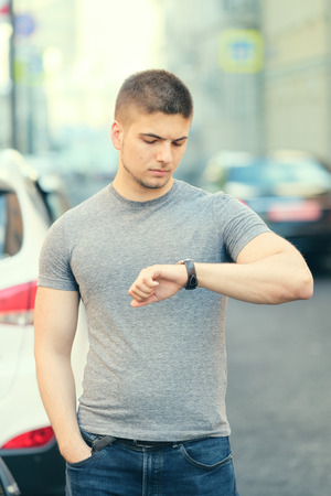 handsome young man: Portrait of handsome young muscular man looking on his wrist watch in urban context