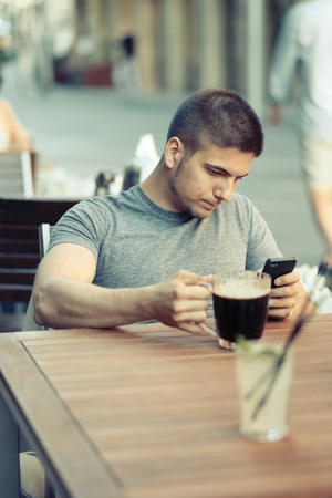 hombre tomando cerveza: Young man with mobile phone drinking beer in outdoor restaurant Foto de archivo