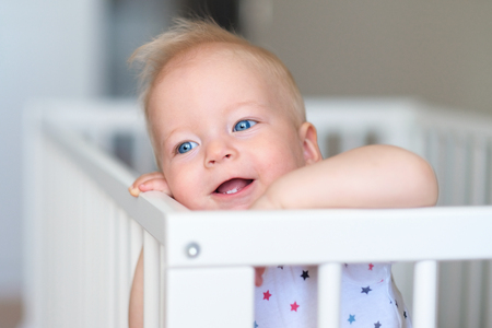 baby blue: Baby boy with blue eyes standing in crib Stock Photo