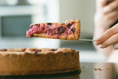 Woman holding wild berry homemade pie slice with raspberries and blueberries. Shallow depth of field. Stock Photo