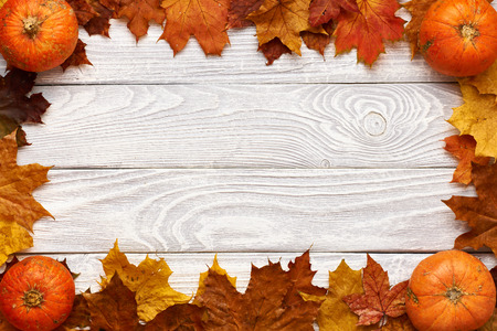 pumpkin border: Autumn leaves and pumpkins over old wooden background with copy space