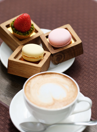 cappuccino cup: Cup of cappuccino and macaroons in outdoor cafe, selective focus