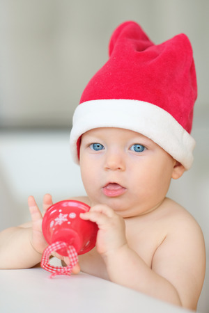 Baby boy with blue eyes christmas portrait in Santa Claus hat Stock Photo