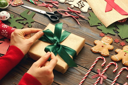 Female hands over christmas gift and homemade gingerbread cookie with handmade decoration on wooden background Stock Photo