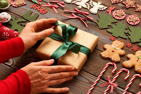 female christmas: Female hands over christmas gift and homemade gingerbread cookie with handmade decoration on wooden background Stock Photo