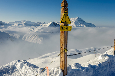 offpiste: Off-piste sign in french language at Alpine winter mountain landscape with low clouds. French Alps covered with snow in sunny day. Val-dIsere, France