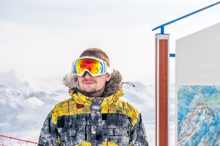 tranquil: Young man in ski goggles outdoors with French Alps covered with snow at background. Val-dIsere, France Stock Photo