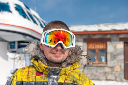 station ski: Young man in ski goggles outdoors with ski lift station in mountains at background. Val-dIsere, France Stock Photo