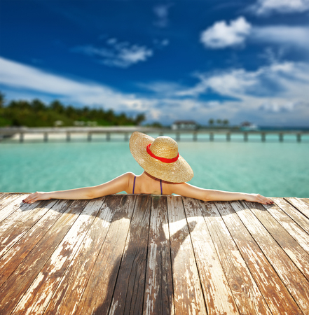 relaxing beach: Woman in hat relaxing at beach jetty