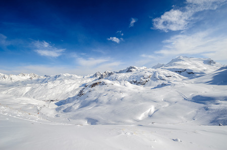 sunny cold days: Alpine winter mountain landscape. French Alps covered with snow in sunny day. Val-dIsere, France Stock Photo