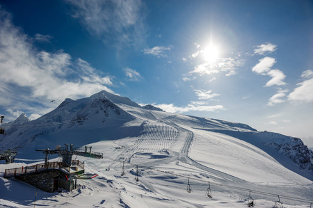 Ski lift station in mountains at winter. Alpine winter mountain landscape. French Alps covered with snow in sunny day. Val-dIsere, Alps, France Stock Photo