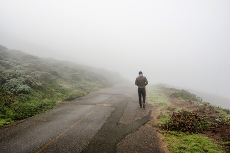 fog white: Lone man walking along the road through white fog Stock Photo