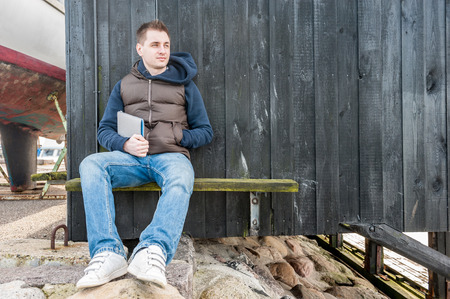 Man holding tablet pc sitting on a bench in front of wooden wall photo