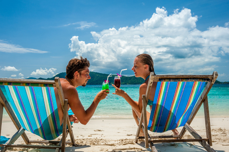 romantic beach: Couple in loungers clinking their glasses on a tropical beach at Thailand Stock Photo