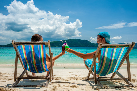 Couple in loungers clinking their glasses on a tropical beach at Thailand Stock Photo