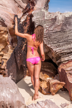 pink bikini: Woman wearing pink bikini on a rocky beach in Thailand Stock Photo