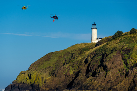 desilusion: North Head Lighthouse at Pacific coast, Cape Disappointment, built in 1898, WA, USA. Coast guard helicopters in the sky. Foto de archivo