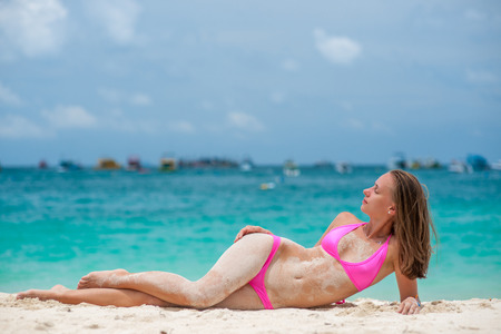 pink bikini: Woman wearing pink bikini laying on tropical beach at Thailand