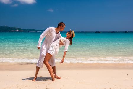 Couple in white having fun on a tropical beach