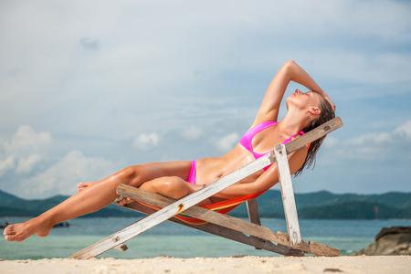 Woman wearing pink bikini in lounger on tropical beach at Thailand