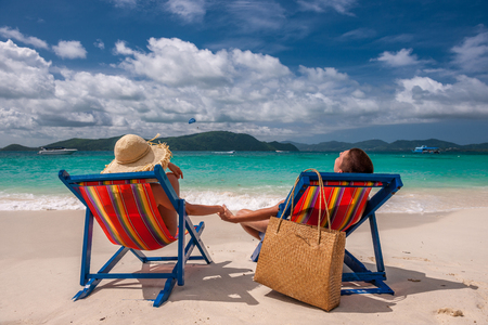 beachbag: Couple on tropical beach in loungers at Thailand Stock Photo