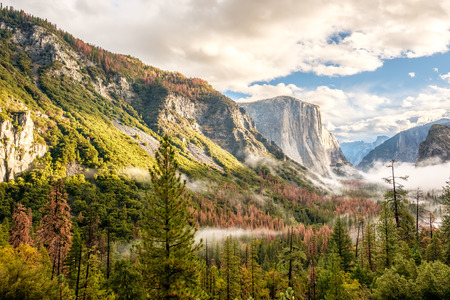 valley view: Yosemite National Park Valley at cloudy autumn morning from Tunnel View. Low clouds lay in the valley. California, USA.