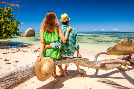 Couple relaxing on a tropical beach Anse Source dArgent at Seychelles, La Digue.
