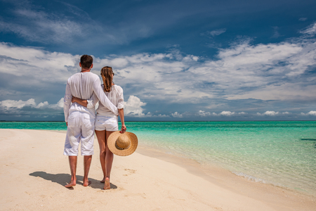 sunhat: Couple in white walking on a tropical beach at Maldives Stock Photo