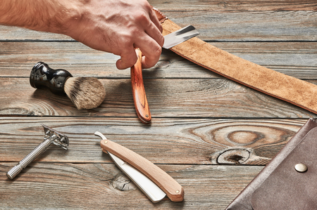 sharpening: Man stropping straight razor with leather tool against old wooden background