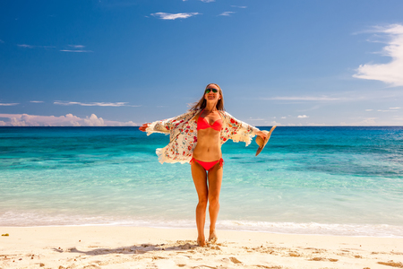 sunhat: Woman with sarong on beach Anse Intendance at Seychelles, Mahe Stock Photo
